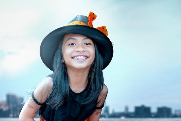 Азиатская детская девочка с костюмом ведьмы и шляпой на хэллоуин Premium Фотографии