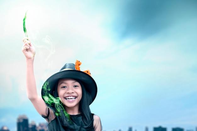 Азиатская ведьма маленькая девочка с помощью палочки с волшебным блеском Premium Фотографии