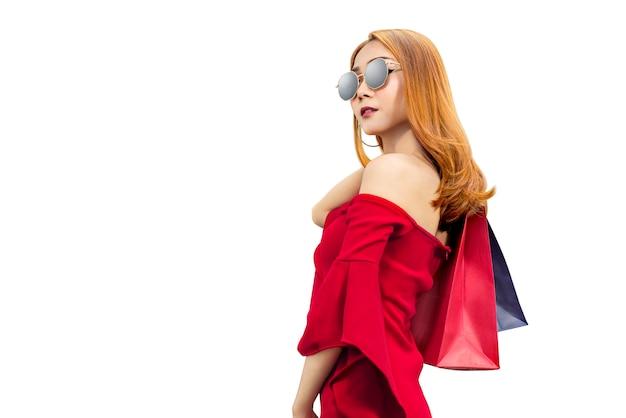 Азиатская женщина в красной одежде и солнцезащитные очки, перевозящих сумки Premium Фотографии