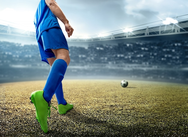 Вид сзади азиатского футболиста, пинающего мяч на футбольном поле Premium Фотографии
