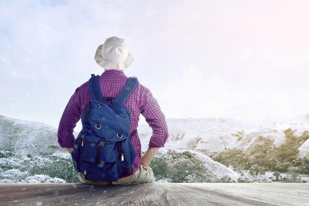木製の床に座って、雪山を見てバックパックと帽子のアジア人の背面図 Premium写真