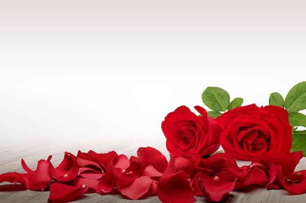 Красная роза и лепестки роз на деревянном столе с белым фоном Premium Фотографии
