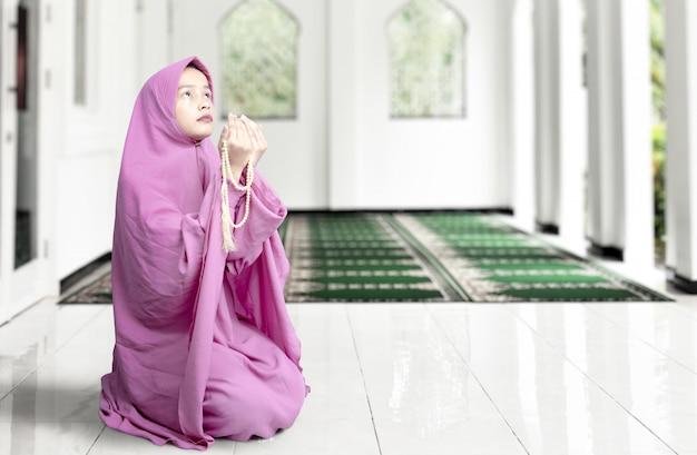 座っていると彼女の手に数珠で祈るベールのアジアのイスラム教徒の女性 Premium写真