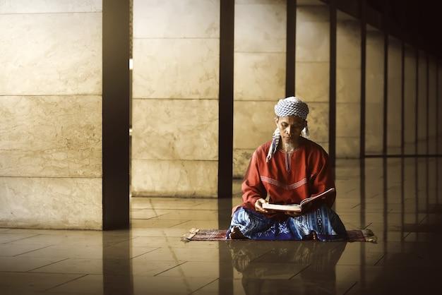 宗教的なイスラム教徒の男性が聖なるコーランを読む Premium写真