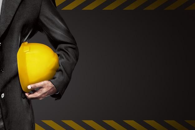 エンジニアの手や腕は労働者のための黄色のプラスチック製のヘルメットを握る Premium写真