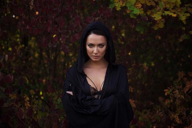 Молодая женщина в черном плаще в осеннем лесу Premium Фотографии