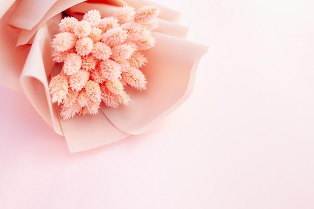 木製の白い背景の上の乾燥したピンクの花の美しい花束 Premium写真