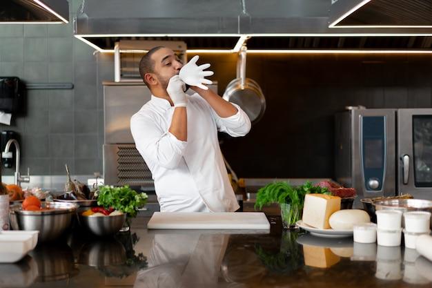 若い男性料理人は彼の保護手袋のジョークを爆破し、プロのキッチンで楽しんでいます Premium写真
