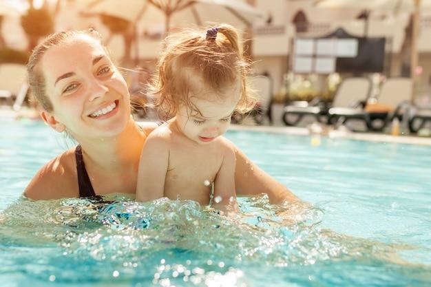 ママと幼い娘はオープンプールで遊んでいます。 Premium写真
