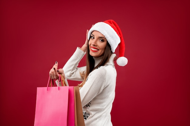 赤い壁に赤いサンタ帽子で肖像画美しい白人女性を閉じます。クリスマス新年のコンセプト。かわいい女性の歯は買い物袋と肯定的な感情を笑っています。 Premium写真