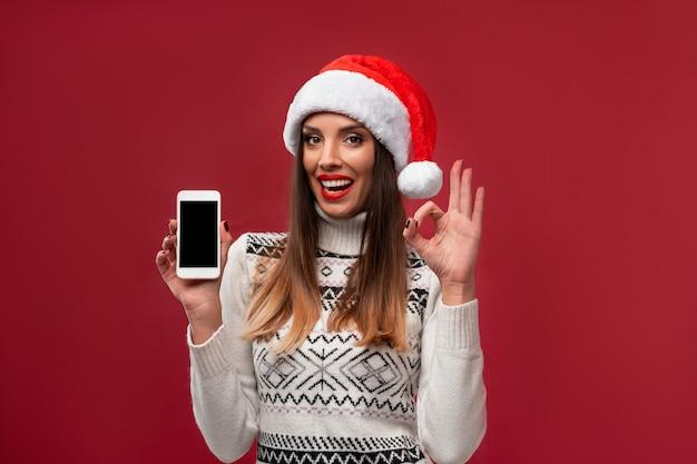 赤い壁に赤いサンタ帽子で肖像画美しい白人女性を閉じます。クリスマス新年のコンセプト。無料のコピースペースで肯定的な感情を笑顔かわいい女性の歯 Premium写真