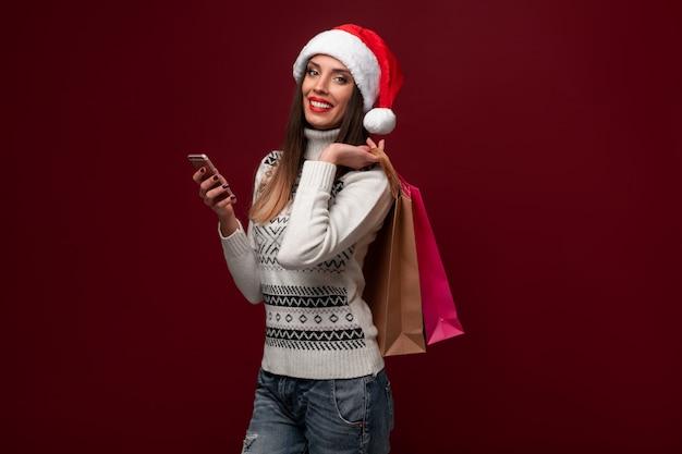 赤い壁に肖像画美しい白人女性サンタ帽子。クリスマス新年のコンセプト。ショッピングバッグと電話オンラインショッピングで肯定的な感情を笑顔かわいい女性の歯 Premium写真