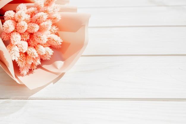 木製の白い背景にドライのピンクの花の美しい花束。 Premium写真