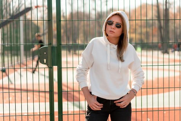 Открытый крупным планом портрет молодой красивой женщины с длинными волосами в солнцезащитные очки, одетый в белый свитер с капюшоном, возле спортивной площадки. молодежная культура летнее времяпрепровождение Premium Фотографии