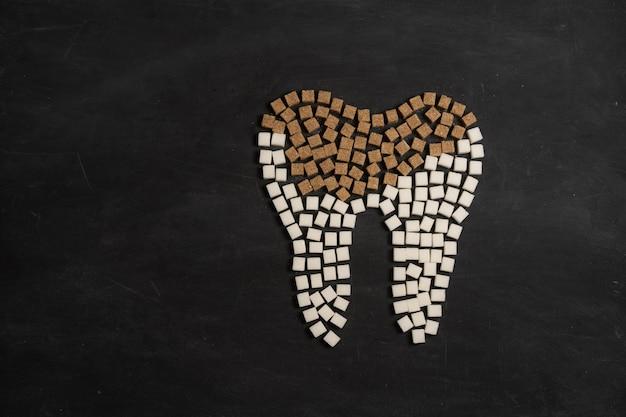 砂糖が歯のエナメル質を破壊する虫歯を導くホワイトシュガーキューブシェイプフォーム歯ブラウンシュガーカリエス黒の背景ヘルスケアと医学口腔病学の概念甘い食べ物が歯を破壊する Premium写真