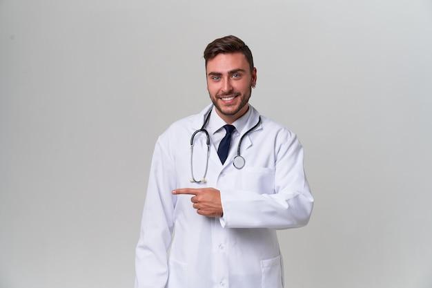 Молодой красивый современный доктор в белой медицинской мантии стоит в студии на белизне. студент-стажер медицинского университета. Premium Фотографии