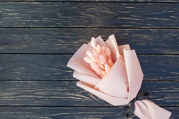 木製の黒い背景にドライのピンクの花の美しい花束。 Premium写真