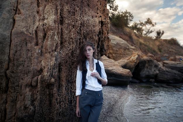 ビジネスの女性のスーツのベストと海のコストに大きな石の近くに立っている白いシャツ Premium写真
