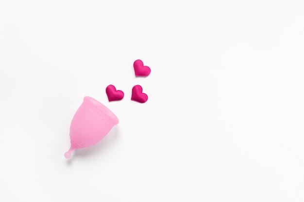 深紅色の心と白い背景の上のピンクの月経カップ Premium写真