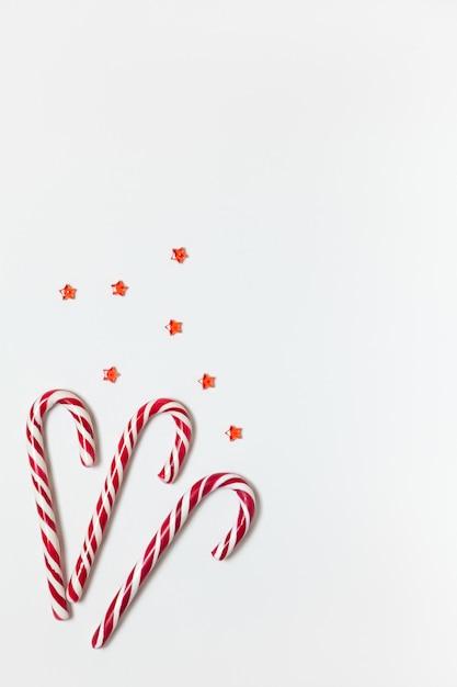Рождественская композиция три карамельные леденцы, конфетти звезды на белом фоне с копией пространства. Premium Фотографии