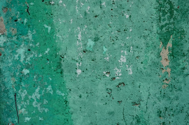 塗料と日光の穴の汚れと緑の織り目加工のぼろぼろの壁の背景。 Premium写真