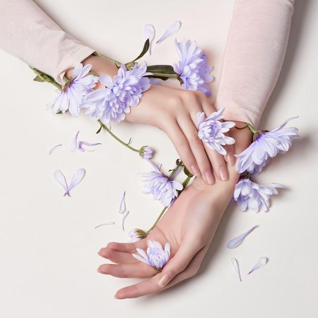 ファッションアートスキンケア手と青い花の女性 Premium写真