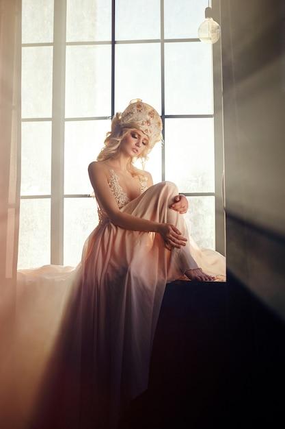 日光の窓に座っている美しい金髪の女性 Premium写真