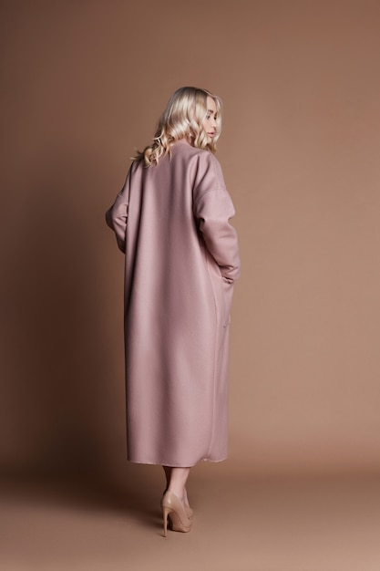 美しい金髪女性がピンクのコートでポーズ Premium写真