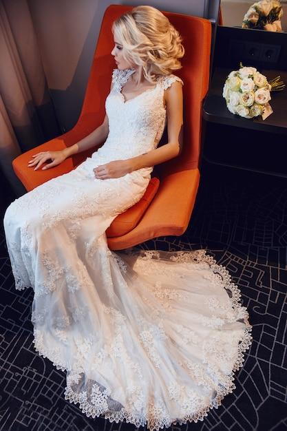 椅子に座っている花嫁金髪白いウェディングドレス Premium写真