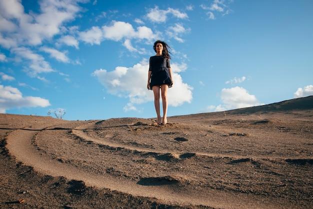 砂の中で跳ねるライフスタイルの肖像画の女性ブルネット Premium写真