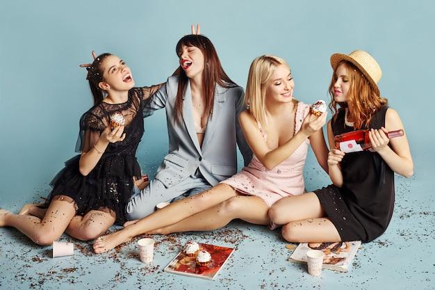 女性が楽しんで休日のパーティーを祝うケーキを食べる Premium写真