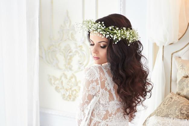 ランジェリーと花輪を持つ美しい花嫁 Premium写真