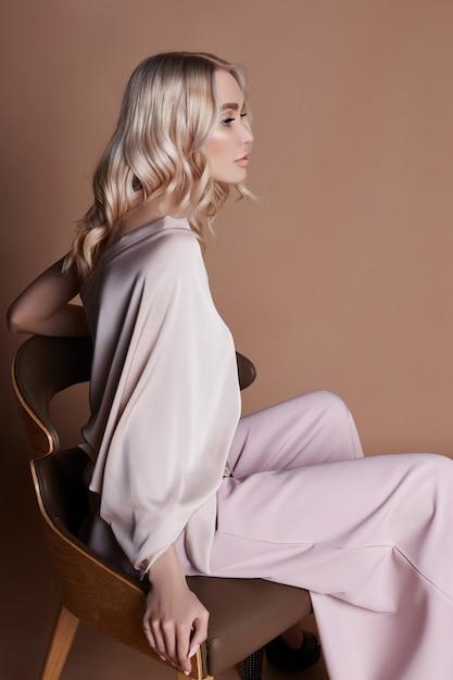 椅子に座っているドレスでセクシーな豪華な女性。秋のコレクション Premium写真