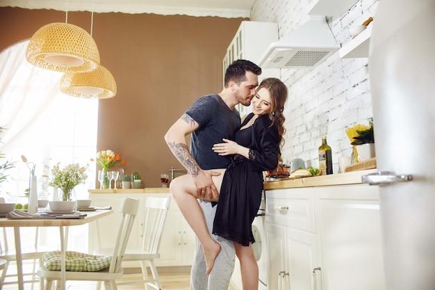 キッチンの朝の愛のカップルが抱擁し、朝食を準備します Premium写真