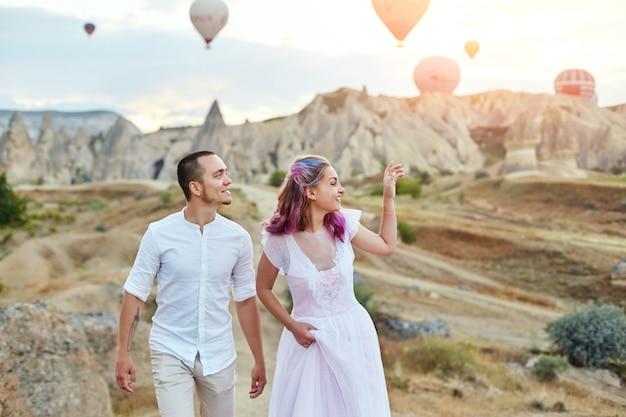 カッパドキアの風船に対する日没の愛のカップルの日付 Premium写真