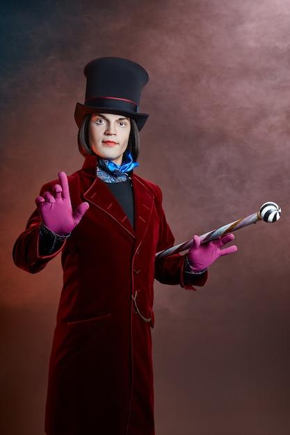 帽子と煙でポーズをとって赤いスーツの素晴らしいサーカス男 Premium写真