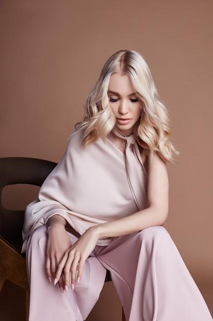 椅子に座っているドレスでセクシーな豪華な女性。女性服の秋コレクション Premium写真