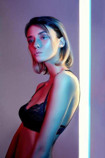 ランジェリーのネオンの光でセクシーな女性。ネオンと光のまぶしさ Premium写真