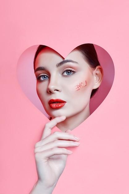 心の穴、明るく美しい化粧、大きな目で探している女性 Premium写真