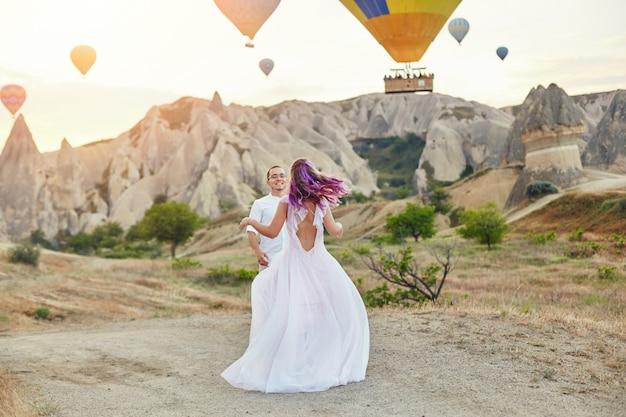 愛のカップルは、カッパドキアの風船の背景に立っています。 Premium写真