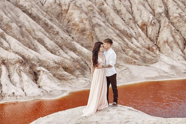 カップルは山の崖と赤い湖の上に立って抱き締める Premium写真