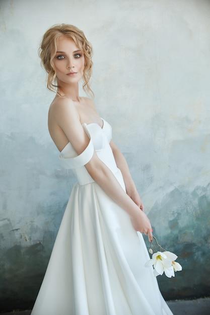 床に座ってシックなロングドレスの女の子。白いウェディングドレス Premium写真