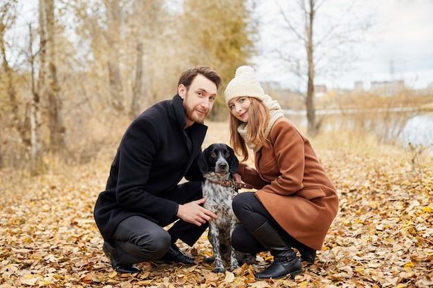 暖かい秋の日に愛のカップルは、陽気な犬スパニエルと公園を散歩します Premium写真
