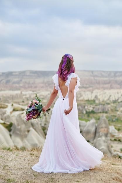 Красивое белое длинное платье на теле женщины. прекрасная невеста с розовыми волосами танцует. женщина с красивым букетом цветов в руках танцует на горе в лучах рассветного заката Premium Фотографии