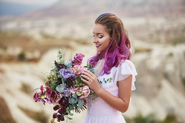 Женщина с красивым букетом цветов в руках стоит на горе в лучах рассветного заката. красивое белое длинное платье на теле женщины. идеальная невеста с розовыми волосами Premium Фотографии