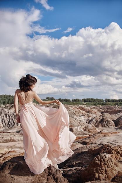 Брюнетка в розовом платье стоит на скале, ветер взъерошивает платье, нежный образ женщины. сказочный горный пейзаж. женщина ветра Premium Фотографии