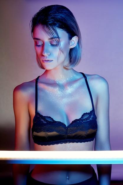 ランジェリーのネオンの光でセクシーな女性。ネオンと少女の顔のまぶしさ。明るいコントラストの光の背景にスパンコールで裸の女性。彼女の顔に美しいメイクとブロンド Premium写真