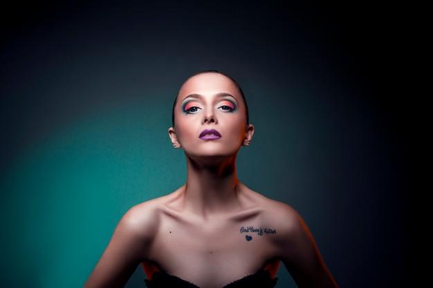 赤い髪の女性少女の顔に美容アートメイク。緑の背景に大きな青い目を持つ完璧な女の子。顔と体のスキンケアのためのプロの化粧品 Premium写真