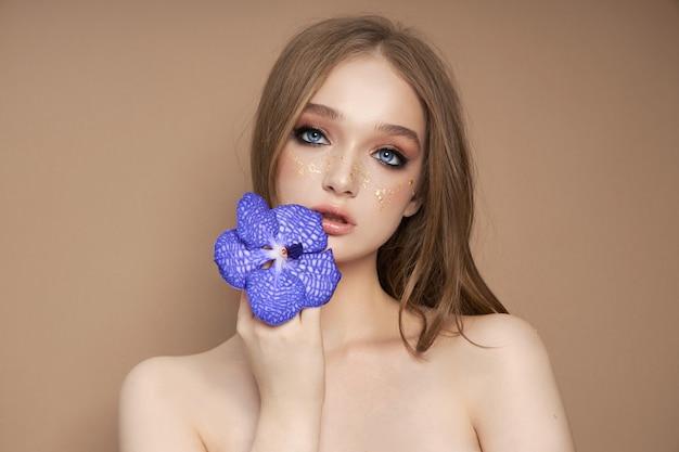 手に青いバンダオーキッドを持つ女性の美しさの肖像画。 Premium写真