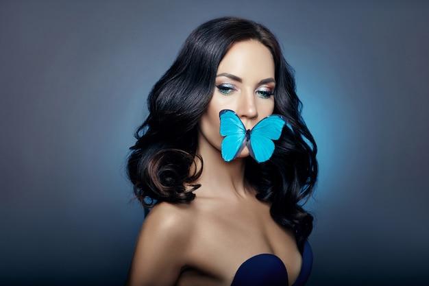 Красивая загадочная женщина бабочки голубого цвета Premium Фотографии